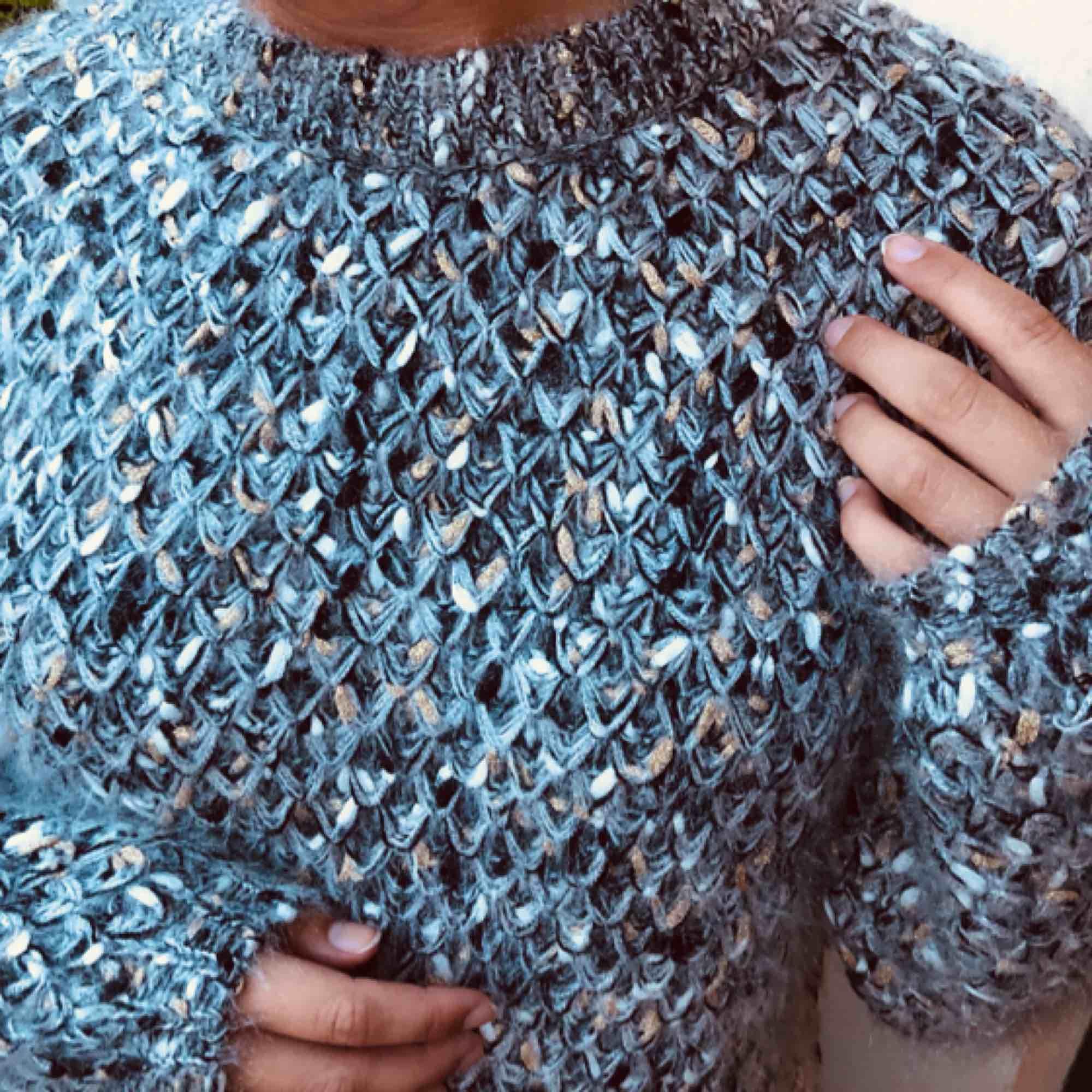 Fin stickad tröja med ballongärm, virkad i blå/grå/guldglitter.. Stickat.