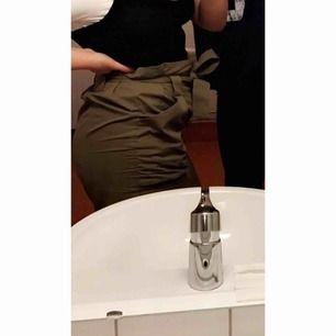 """Snygg kjol från HM, det står att den är strl 42 men snarare 38. Militärgrön """"paperbag"""" kjol i bra skick, endast använd 1-2 gånger. Frakt ingår ej"""