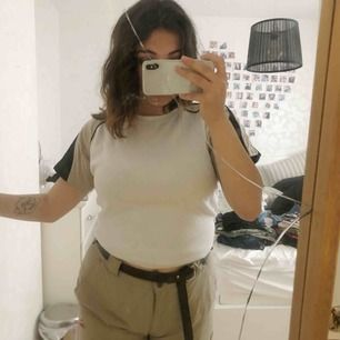 En vit oversize t-shirt med beiga och svarta detaljer! jätte fin till de beiga byxorna jag har på bilden som jag också säljer (hitta inlägg i min profil). 50kr + frakt!