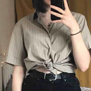 Kortärmad skjorta köpt på secondhand. Från H&M från början. Skulle säga att den är ganska kall beige i tonen med svarta smala ränder över hela. Snygg att exempelvis ha över en svart polotröja! Jag är 168cm! Priset kan diskuteras :)
