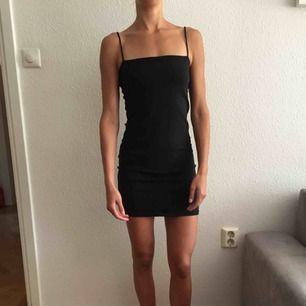 Snygg enkel tajt svart klänning i bomull från ginatricot.
