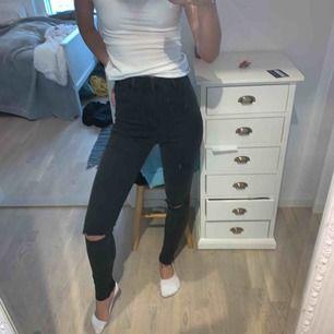 Högmidjade svarta jeans med hål på knäna. Aldrig använda eftersom att jag fick de i present och de inte passar min stil. Väldigt stretchigt material.