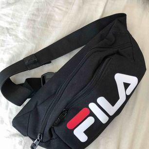 En axelremsväska / waistbag från Fila. Köpt på Urban Outfitters i Stockholm 2017 & använd OTROLIGT sparsamt, alltså nyskick.