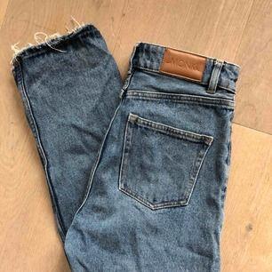 """Säljer mina blåa mom-jeans från Monki. Modellen heter """"Kimono High Relaxed"""". Har själv gjort ristningarna längst ner vilket jag personligen tycker är supersnyggt. Använda en del men inget som syns! Frakt = 79kr"""