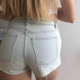 Ljusblå shorts med knappstängning & slistar i sidorna
