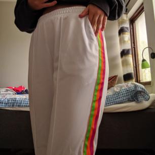 Vita, snygga byxor med regnbågsmönster. Nya från junkyard, aldrig kommit till använding därav prislappen:))