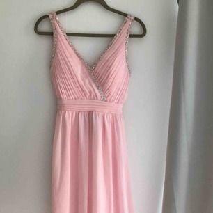 Ljus rosa lång balklänning med sten detaljer på fram och baksida. Köptes i Stockholm på butiken Scala (webbshop miinto.se) och är använd 1 gång. Ordpris 1299kr, säljs för 800kr. Köparen står för frakt.