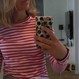 En rosa/vit randig tröja från NAKD. Använt ca 3 gånger. Stretchig och i skönt material. Jag är 170 cm och den XS passar även fast jag brukar ha S i allt annat. Ny pris: 150kr. Mitt pris: 80kr.