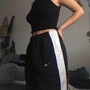 Nike tracksuit byxor med gula detaljer 🤩 Väl använda men fortfarande i gott skick! Det står L men de passar mig super som bär S, dock går de att spänna vid midjan om det skulle vara ett problem!