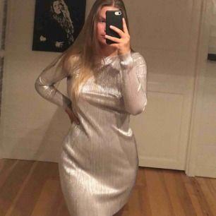fint klänning med reflekterande silvrig material från Nelly, aldrig använd och har fortfarande prislappen kvar. Köparen står för frakt😛