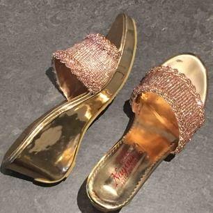 Glittriga/Skimmrande sandaler med diamanter/stenar i roséguld färg. Jättefina!!! Perfekt till sommaren! De ser underbart på solbränd hud! Stl 38 men snarare 37. Helt nya. Säljs pga fel storlek.