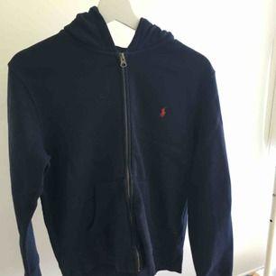 En navyblå hoodie från ralph lauren i fint men använt skick. Säljes då den blivit för liten. Storlek L, junior