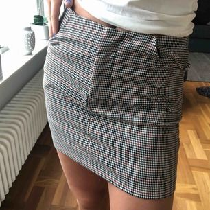 Tajt kjol från Bershka. Den är rutig med vitt, svart och rött. den har två fickor.