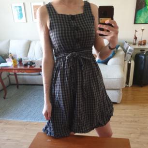 Rutig klänning med snörning runt midjan! Står ingen storlek men jag gissar att den går att ha upp till M.  Kan hämtas i Umeå eller så kommer vi på lösning för frakt:)