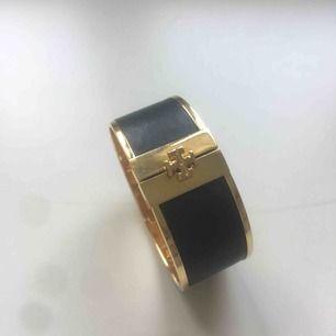 Svart Tory Burch armband med guldiga detaljer. Superfint skick! Storlek M.  Skriv gärna om ni har frågor