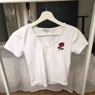 Vit kroppad T-shirt med en ros på vänstra bröstet. Använd en gång och säljer pga att den är för liten. Kan möta upp i Vetlanda eller så står köparen för frakten.