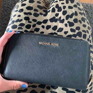 """En helt ny Michael kors plånbok """"jet set travel flat case"""" som köptes för 1195 kr på zalando och säljes nu för 500 kr. Priset kan diskuteras. Kan frakta eller mötas upp i Stockholm"""