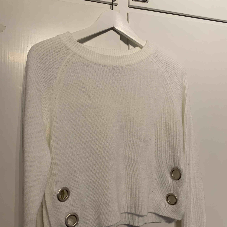 Vit, något croppad tröja med metaldetaljer. . Tröjor & Koftor.