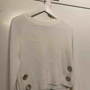 Vit, något croppad tröja med metaldetaljer.