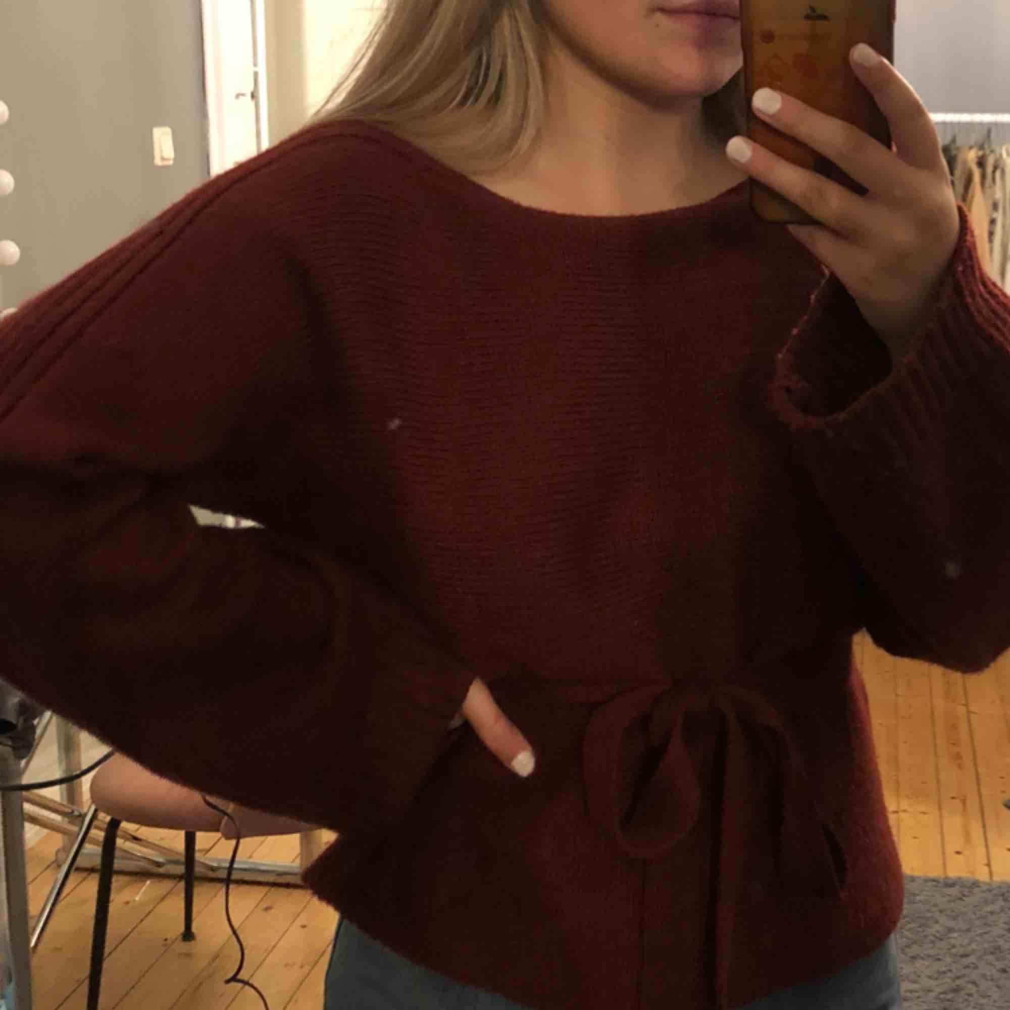 En vi röd stickad tröja med vidare armar och detaljer på, tröjan kommer med ett stickat bälte i samma färg och matrial, tröjan är använd 1 gång. Stickat.