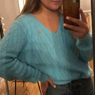 En blå kabelstickad ljusblå ralph lauren tröja med ett oranget märke💕