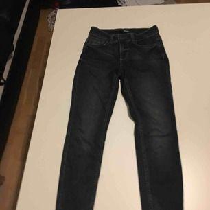 Ett par mörkblåa jeans som nya med en dragkedja i bak av smalbenet