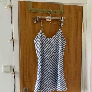 Randig sidenklänning. Köpt på secondhand men aldrig använd av mig. Frakt tillkommer💙💙