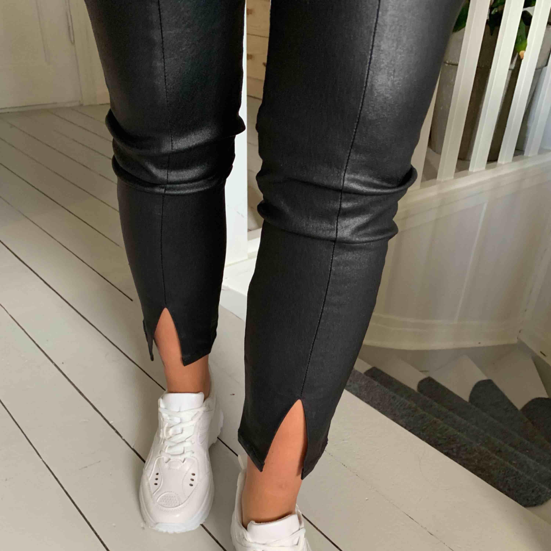 Skitsnygga byxor i läderimitation med slits framtill. Passar XS-M. Aldrig använda . Jeans & Byxor.