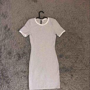 Grå ribbat klänning med vita detaljer för 190 kr ink frakt.