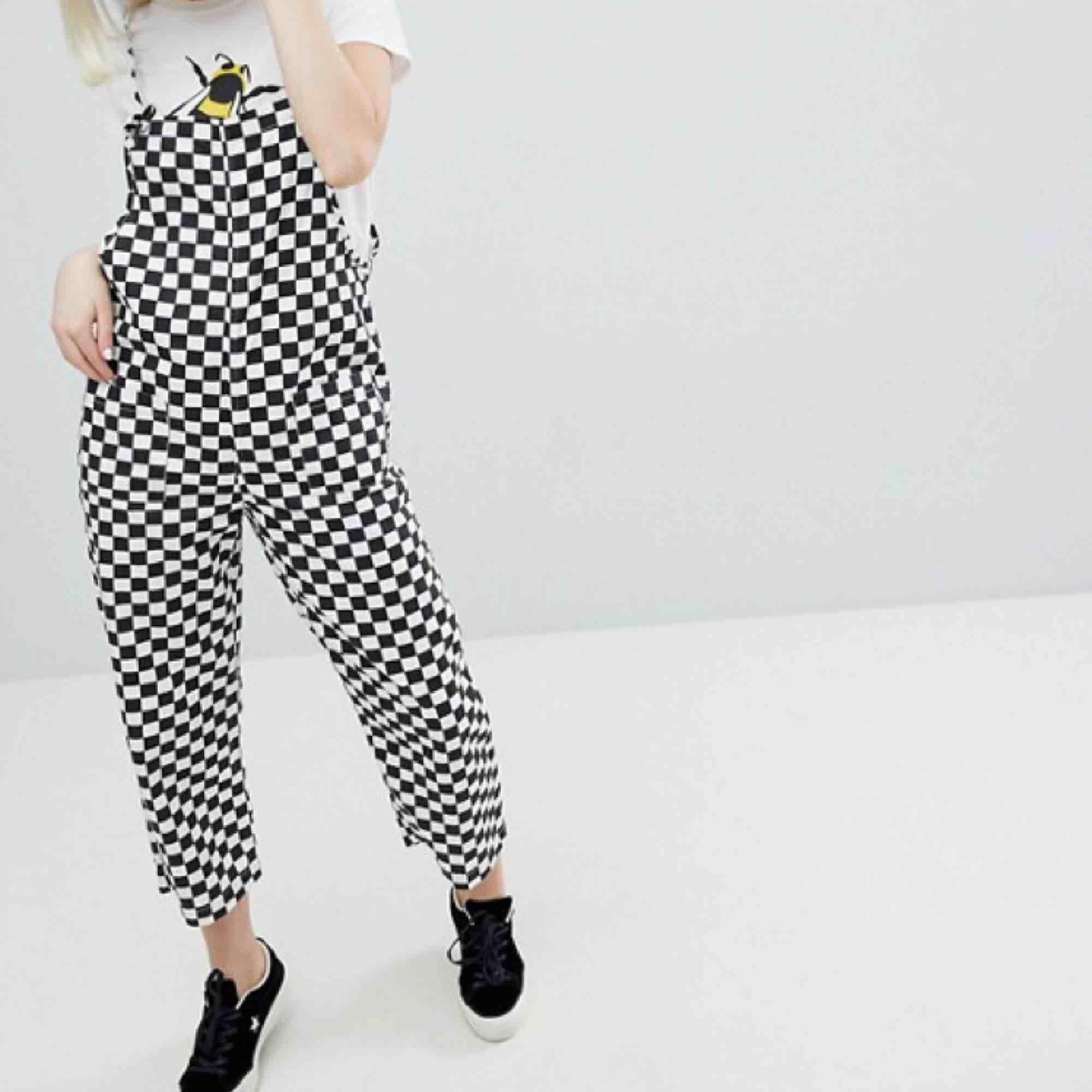 Schackrutiga dungarees från Monki, Storlek S men passar M pga oversize! Knyts och justeras vid axlarna. Helt oanvända pga för stora för lilla jag på 151 cm!. Jeans & Byxor.