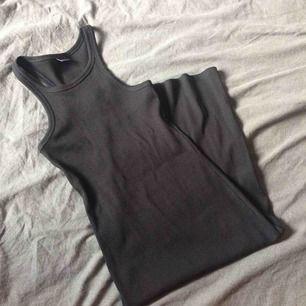 Tight klänning som formar kroppen, med slits nertill. Har aldrig kommit till användning. Fraktkostnaden står jag för.