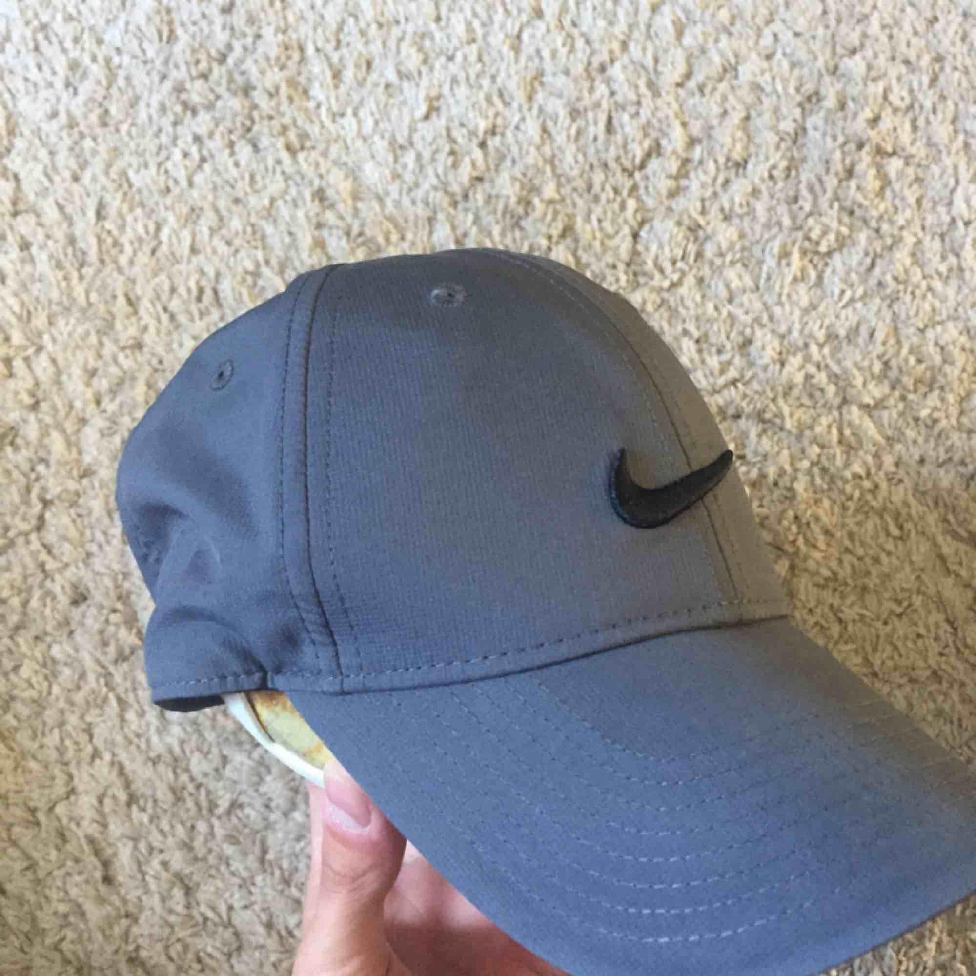 Keps från Nike i mörkgrå färg med svart Nike märke. Polyestermaterial. Helt oanvänd. Bakre halvan av kepsen är tunn. Skön o sval keps som funkar bra till vardags men även till träning :). Accessoarer.