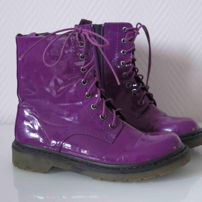 Dr. Martens liknande boots i lila lack. Något stora i storleken. . Skor.
