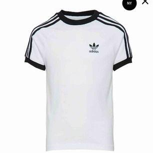 Vit och svart t-shirt med sträck på armarna från Adidas i storlek L. Använd men som ny. Köparen står för eventuell fraktkostnad