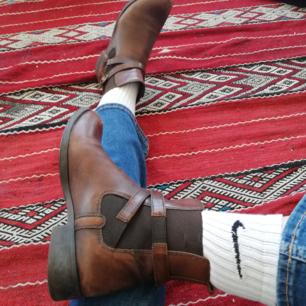 Mörkbruna vintage boots, äkta läder i stl 38. Blivit klackade och sulade i vintras hos skomakare med Vibram-sula. Väl omhändertagna. Bra kvalite+slitstarka, perfekta på festival om det blir lite geggigt. Frakt 63 kr.