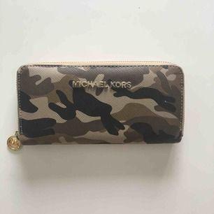 Fake Michael Kors plånbok med militärprint och gulddetaljer. Plånboken är mycket rymlig innehållande 12 kortfack och myntfack samt delare där man kan förvara sedlar och kvitton🌼