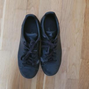 Säljer fina Adidas Stan Smith i helsvart läder. Sparsamt använda, dock slitna vid stortån men fixas enkelt med ex. svart skokräm.