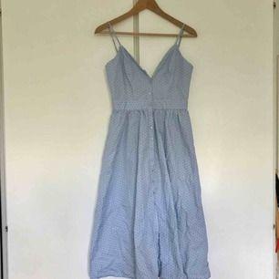 Duvblå ankellång klänning, mörkblå små prickar. Knappar fram, öppen rygg med rosettknytning bak. Ställbara axelband. Helt oanvänd, nu för liten för mig så kan tyvärr inte ta en figurbild😌 Jättefin!!!🙏 Storlek 38 men är en 36. Frakt tillkommer.