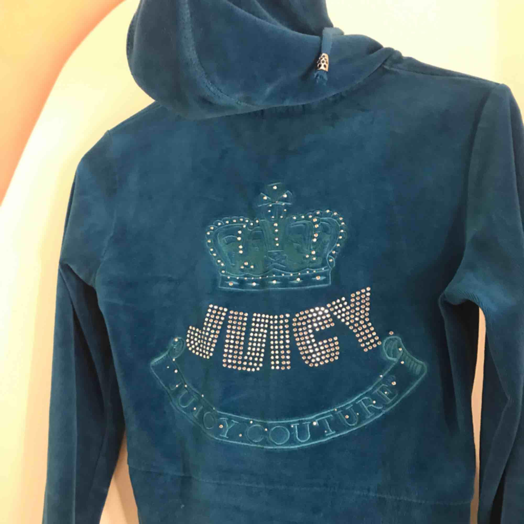 """En blå juicy couture """"fleece"""" eller """"tjocktröja"""". Använd ett fåtal gånger. Väldigt skönt material, den e i storlek M men ja skulle säga att den är liten i sin storlek. Den har en luva o ett stort """"Juicy couture"""" märke på ryggen. Nypris: 1499 kr . Huvtröjor & Träningströjor."""