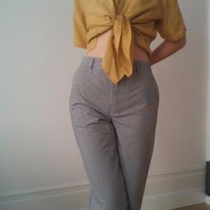 Oanvända långa nästan raka rutiga byxor. Med justerbar midja med hjälp av knappar bal på byxorna, höga i midjan.