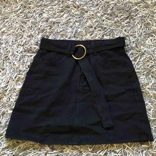 Hej! En svart jeans kjol med ett medföljande skärp av tyg. Det är bara att kontakta för frågor.