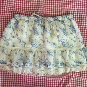 Söt vit kjol med blåa små blommor och vita spetsdetaljer. Aldrig använd så den är i perfekt skick. Frakten är inräknat i priset 🐁