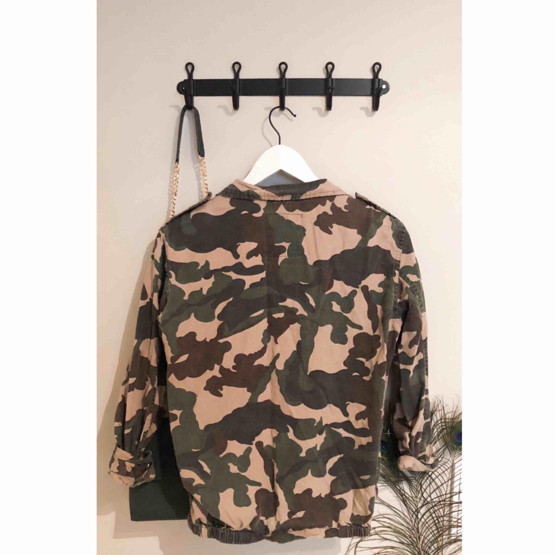 Cool jacka/kavaj i trendigt militärmönster som livar upp vilken outfit som helst!  Är av tunnare jeans-tyg med tryck framtill och små fickor med knappar. . Jackor.
