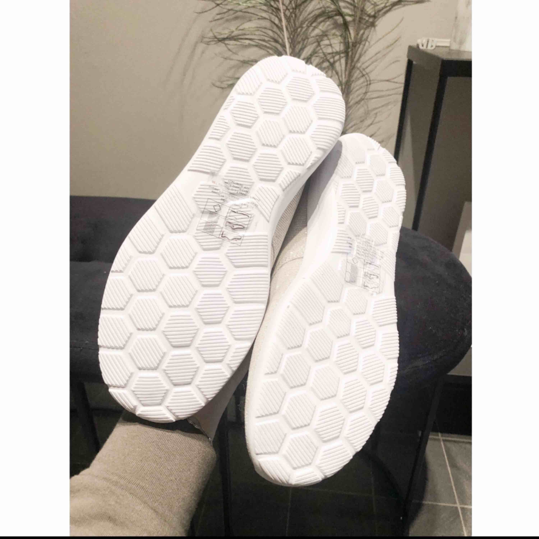 Aldrig använda träningsskor med beige-glittrigt tyg! Skorna är superlätta och sköna att bära och röra sig i.   Snyggare springskor som ligger helt i mode!   Jag kan mötas upp eller frakta, dock ingår inte frakt i priset! . Skor.