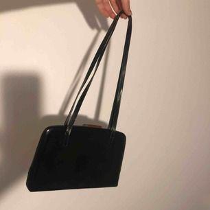 Liten nätt handväska. Svart med litet silverfärgat spänne. Väldigt enkel. Använd men bra skick
