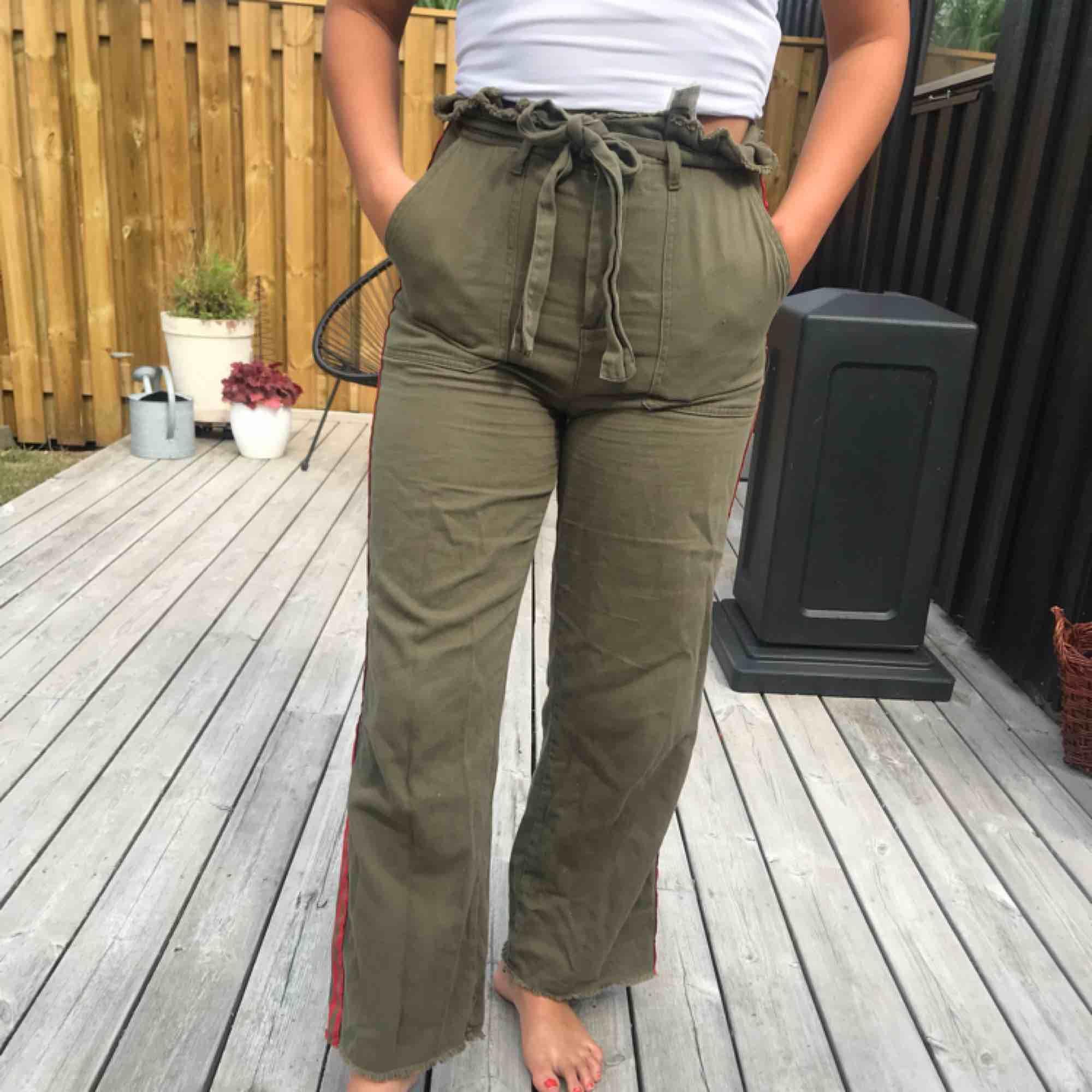 Gröna vida byxor men fina detaljer i midjan och röda streck längs benet! Frakt står köparen för<3. Jeans & Byxor.