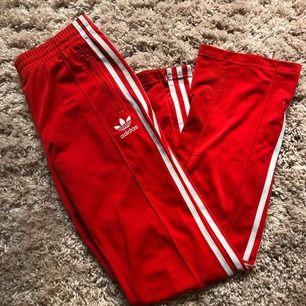 Röda adidasbrallor som är lite utsvängda där nere! Dragkedjor på sidorna så man kan göra dom ännu mer flare :)