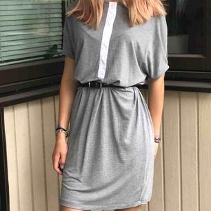 Lång grå klänning med vit knapp ränd fram! Nästan helt oanvänd och bra skick! OBS skärp ingår inte! Kund betalar frakt!