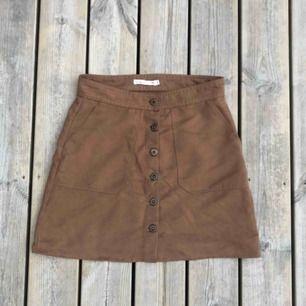 En brun högmidjad kjol från Lager 157 storlek S.