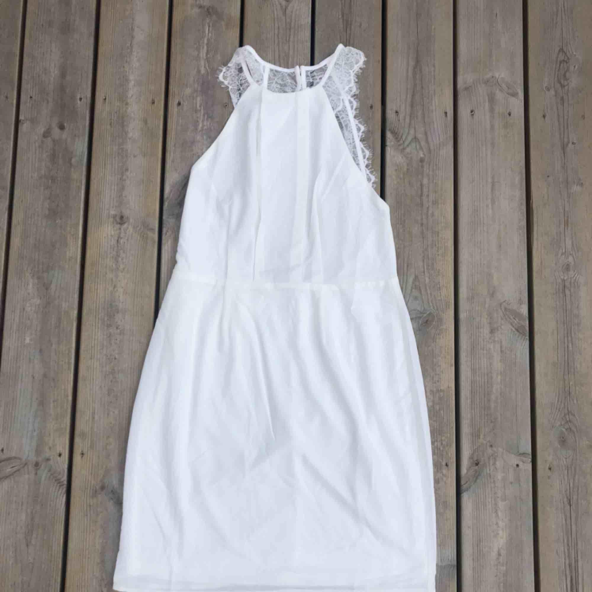 En fin vit klänning från Nelly, storlek 40.   Aldrig använd då den skulle varit min student klänning men köpte en ny. . Klänningar.